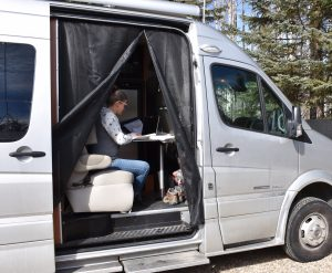 Aimee working in her camperized van.